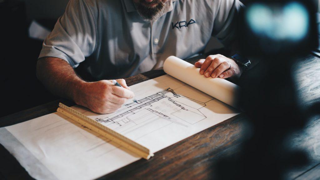 man sketching a building