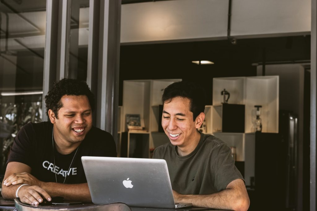 friends laughing while looking at laptop