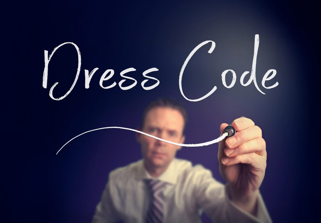 A businessman writing a Dress Code concept with a white pen on a clear screen.