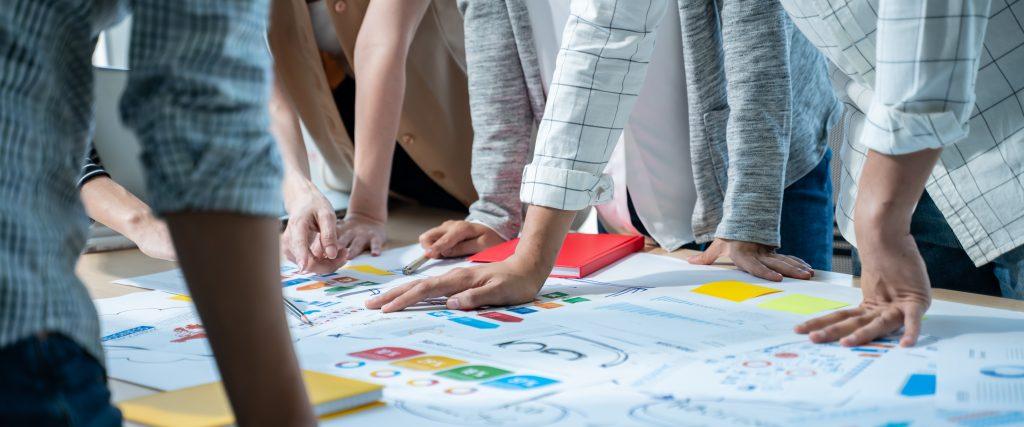 Grupo de presentación de reunión de tormenta de ideas de negocios creativos asiáticos jóvenes, discutiendo la hoja de ruta para el lanzamiento del producto, planificación, estrategia, desarrollo de nuevos negocios, trabajando con un nuevo proyecto de inicio en la oficina.