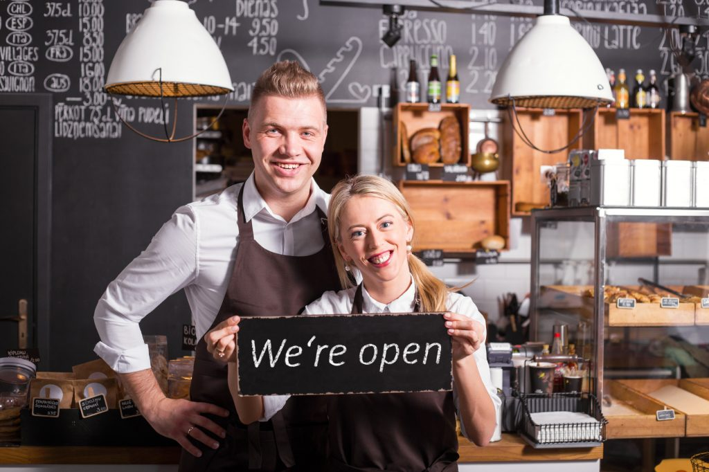 Coffee shop owners showing open sign