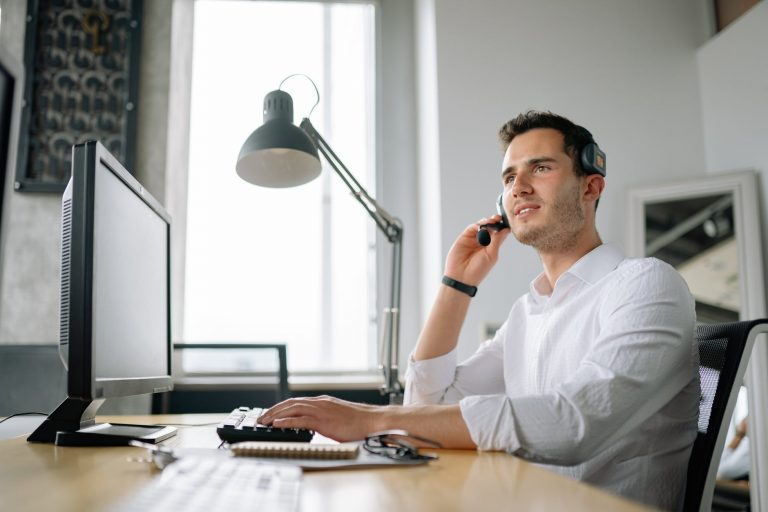 a man in white in front of a computer