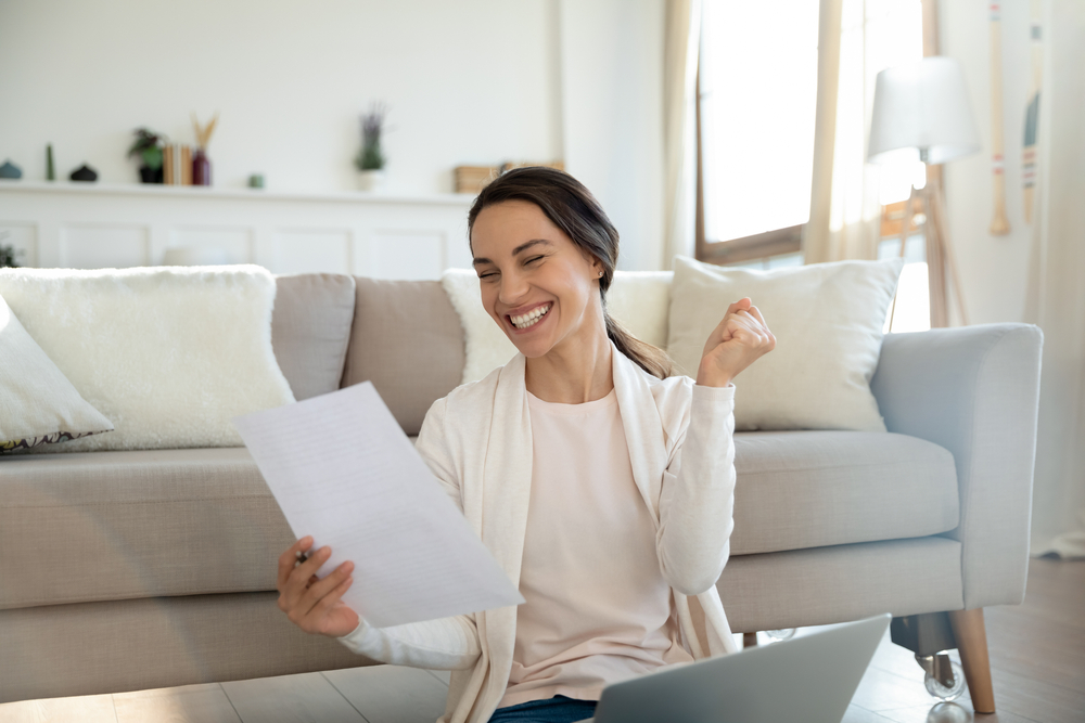 a woman holding a piece of paper with a smile