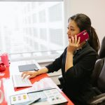 a woman in the office talks over the phone