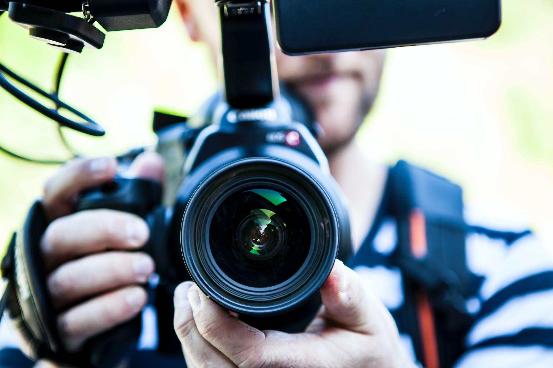 a man holding a camera lens
