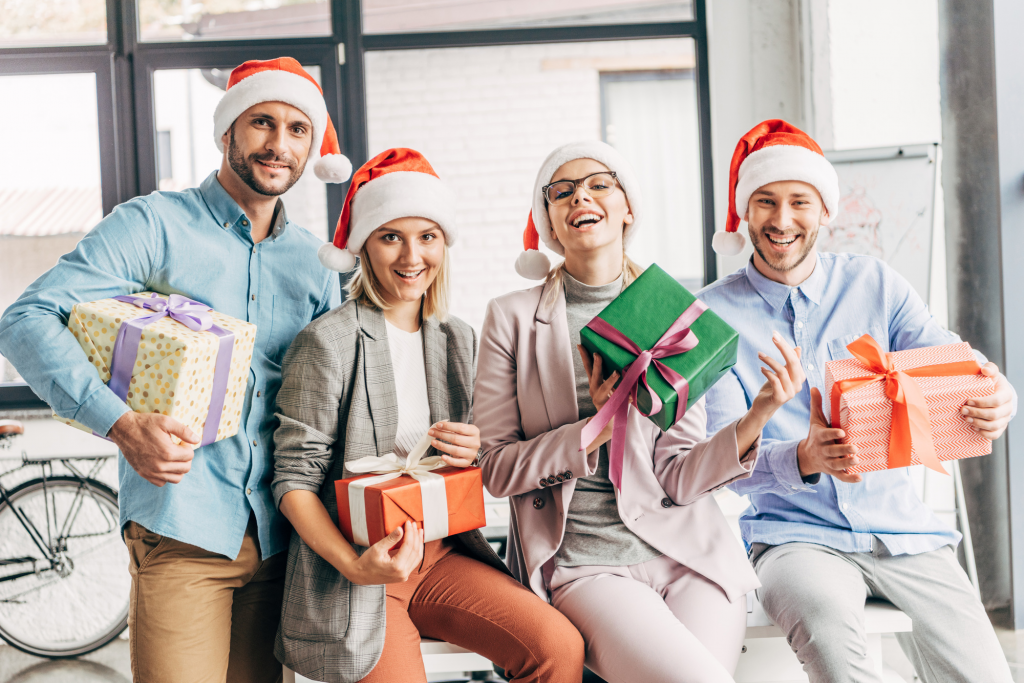four people holding gifts